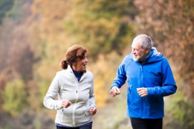 Beautiful active senior couple running together outside in sunny autumn nature