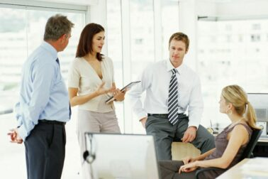 Two businessmen and two businesswomen having discussion in office